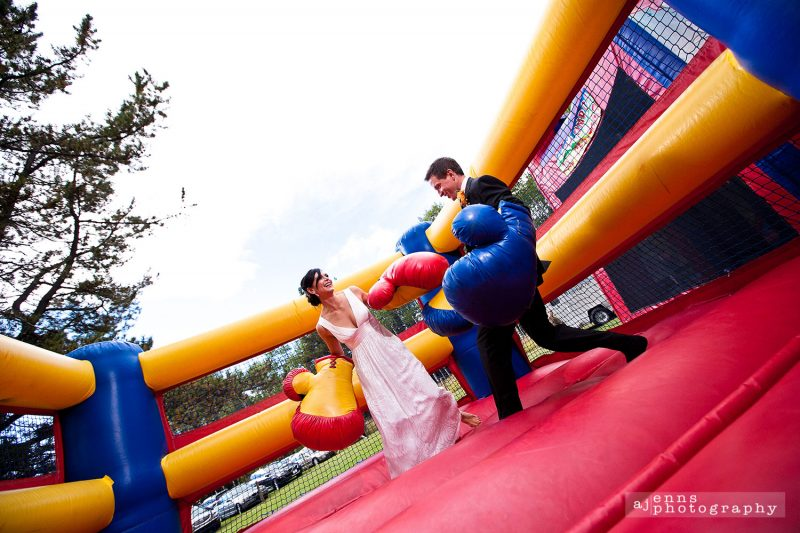 Bride and groom boxing with massive gloves in blow up ring