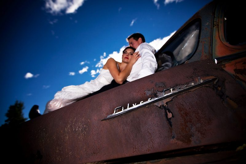 Romantic photo of the couple with the blue sky on the hood of a junker car