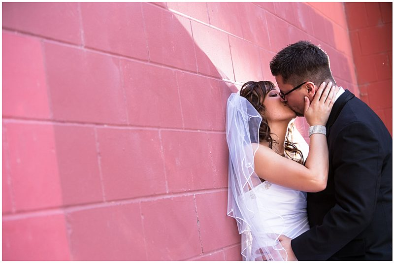 A kiss against and amazing red wall in the heart of the Exchange District in Winnipeg