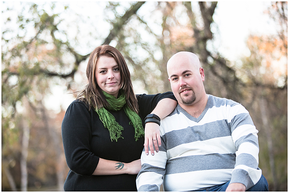 The couple poses on a rock by the duck pond