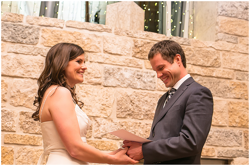 Bride and groom share their vows in front of the fireplace