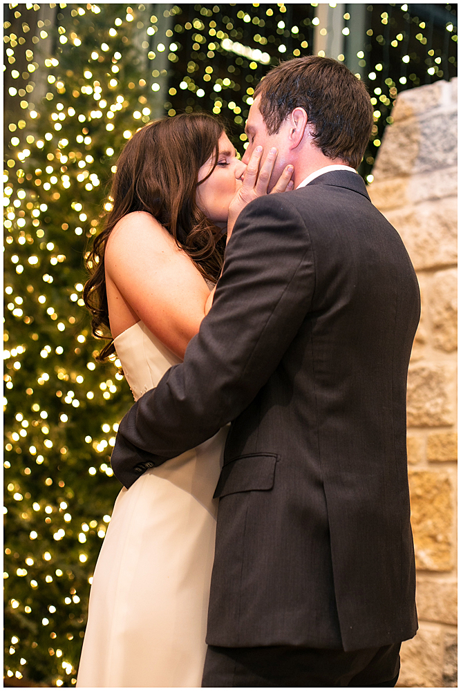 Romantic first kiss in front of the Christmas tree