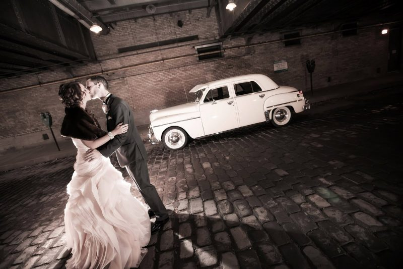 Under the bride at the Forks, Winnipeg for wedding photos with a pearl white limo