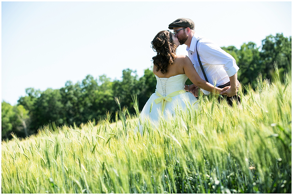 Bride and Groom kissing in the middle of a wheat field