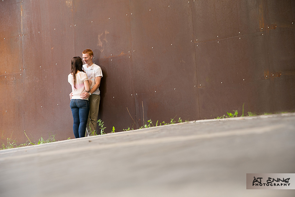 The couple kissing in the distance by a metal rusty wall