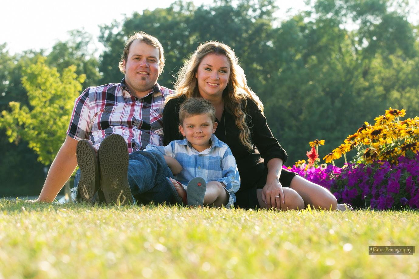 The happy family sitting on the grass by the flowers