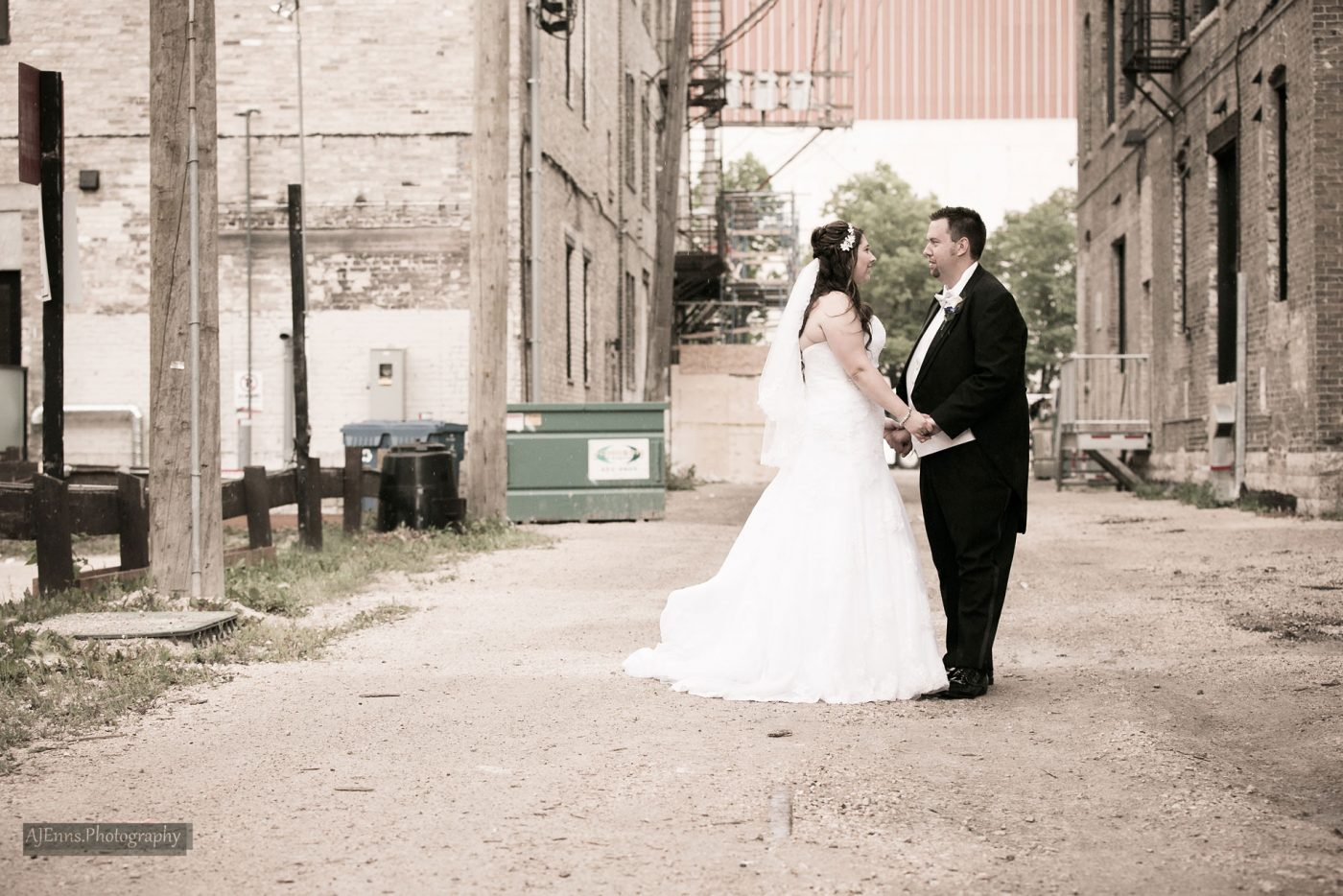 Bride and groom in a back alley in the rain