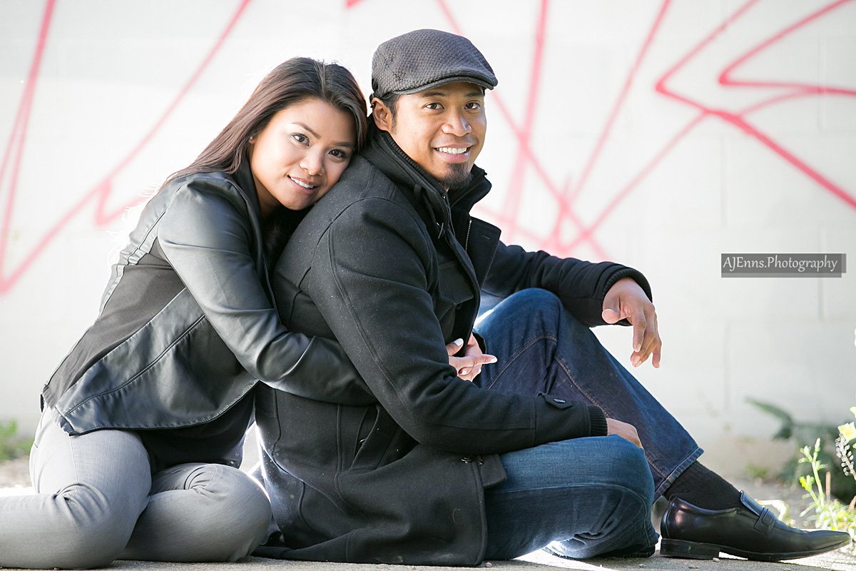 Jaenette hugging Junior from the back in front of a graffiti wall