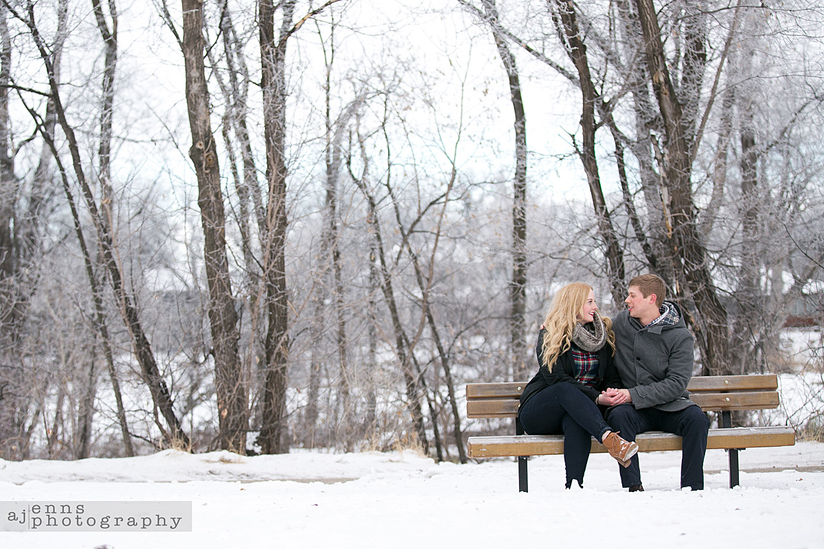 The couple enjoying a park bench in the middle of winter