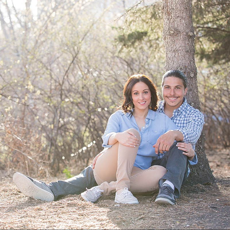 The couple lounges under a spruce tree for their engagement photos.