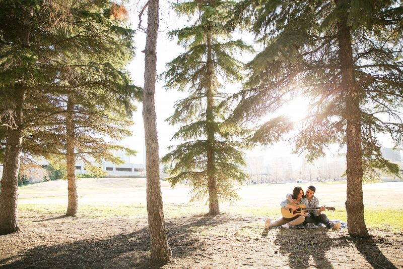 The couple playing guitar under some spruce trees