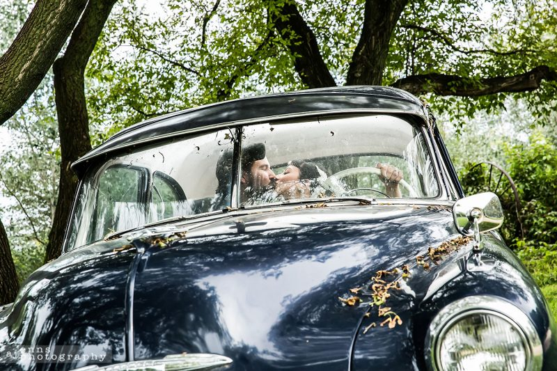 The couple in the front seat of the old car