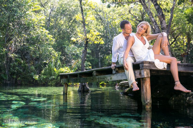 The couple sitting on a dock in a cenote