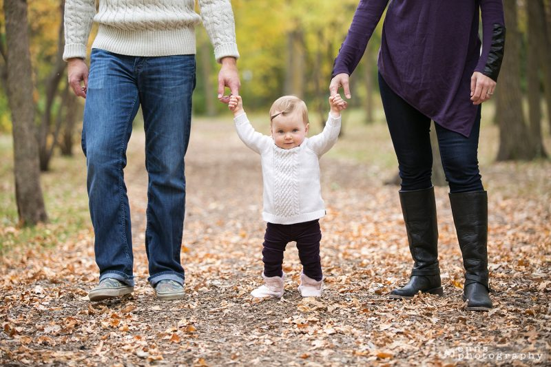 Walking the first steps with the help of Mom and Dad