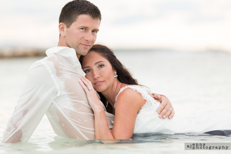 The bride laying on the grooms chest in the water