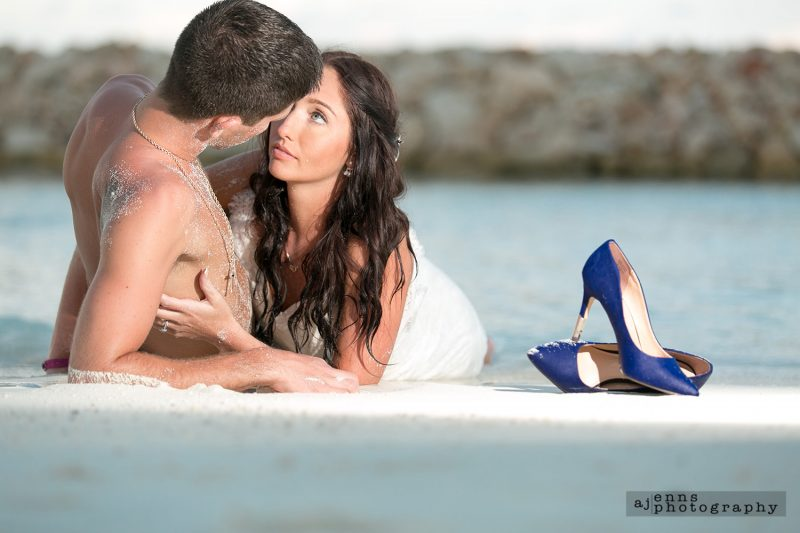 The bride and groom laying on the beach with the wedding shoes close by