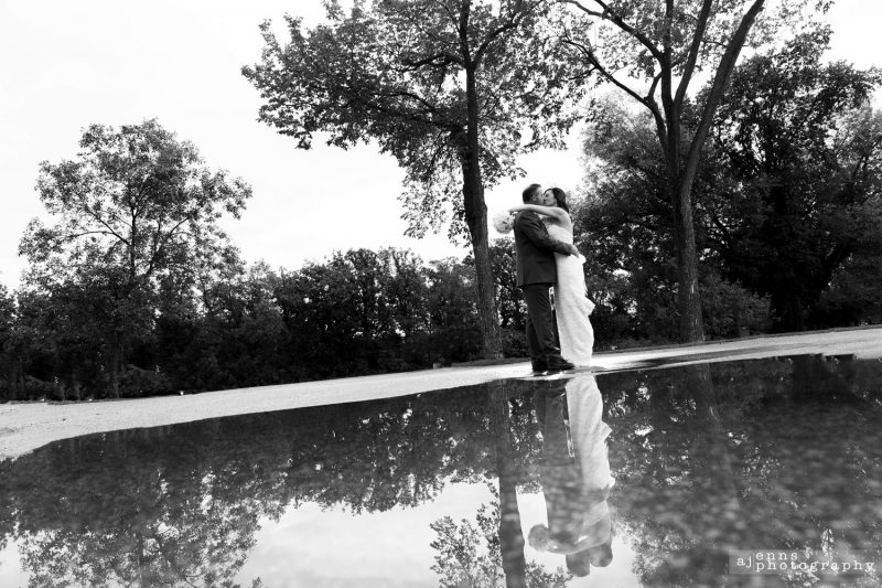 The couple kissing with their reflection in a puddle