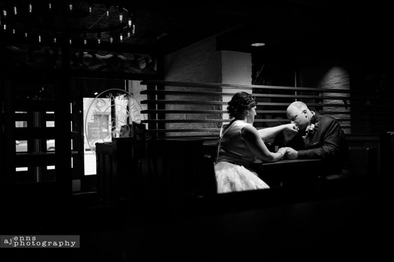 The groom kissing the brides hand under the darkly lit bar