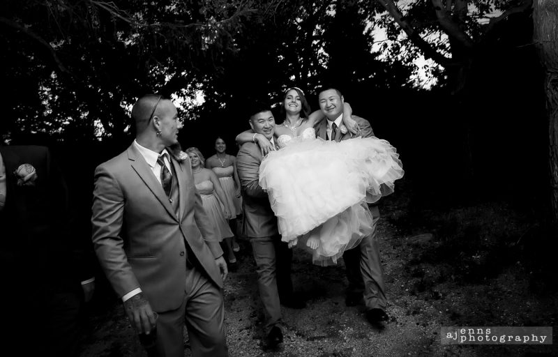 Felicia being carried by her groomsmen over some mud in her wedding dress