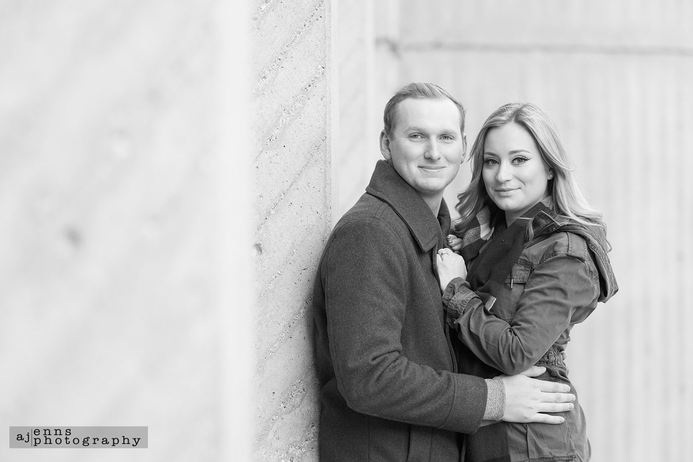 The engaged couple leaning against a brick wall in the Exchange District