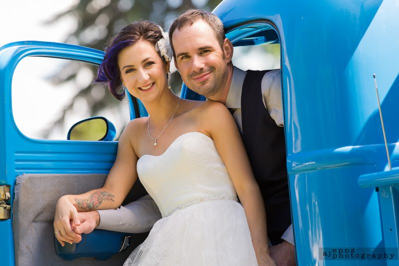 Julie and Darrell in the front seat of the antique blue truck