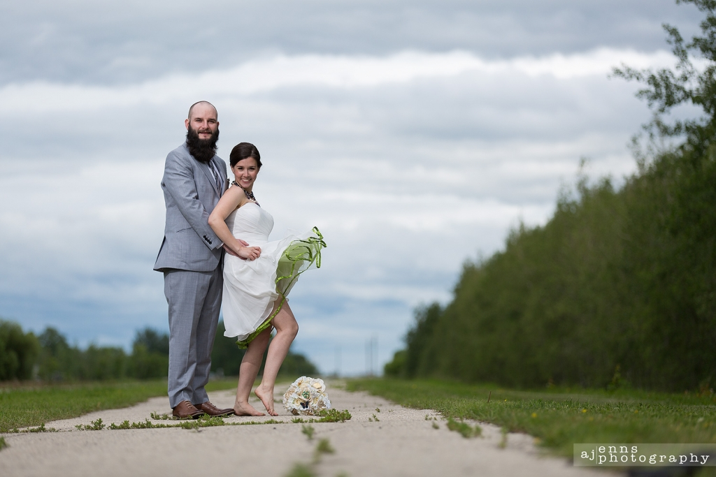 The newlyweds standing on path in the back woods while the bride fills her dress up