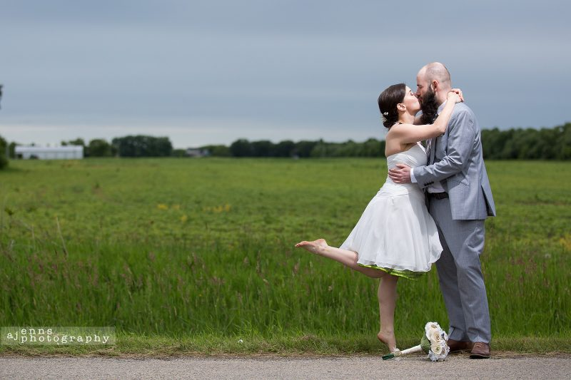 The couple kissing in front of a green field