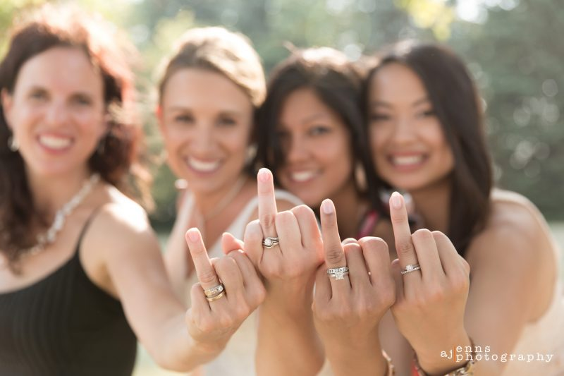 The bride and her friends holding up their wedding ring fingers showing off their wedding rings