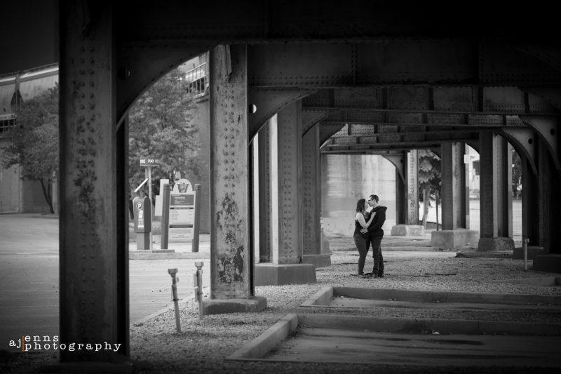 The couple embraces underneath the train bridge