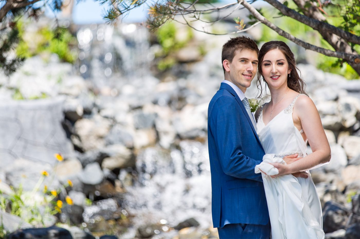 The couple hold each other with a waterfall in the background