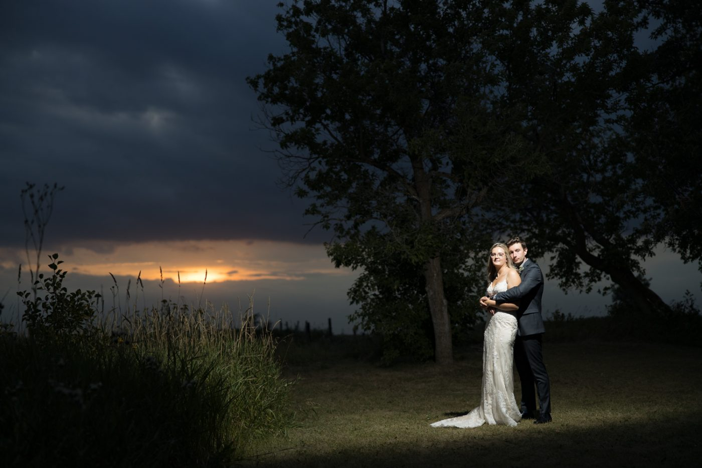 Bride and groom standing under a spotlight in a field with the sun setting in the background