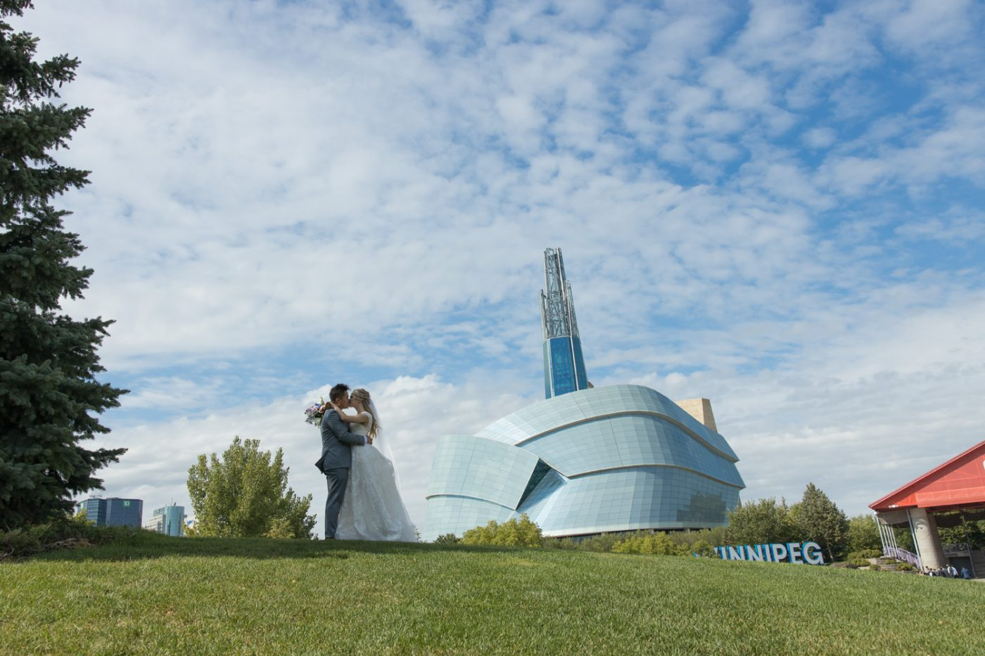 The couple kissing on the top of a hill with the Museum in the background