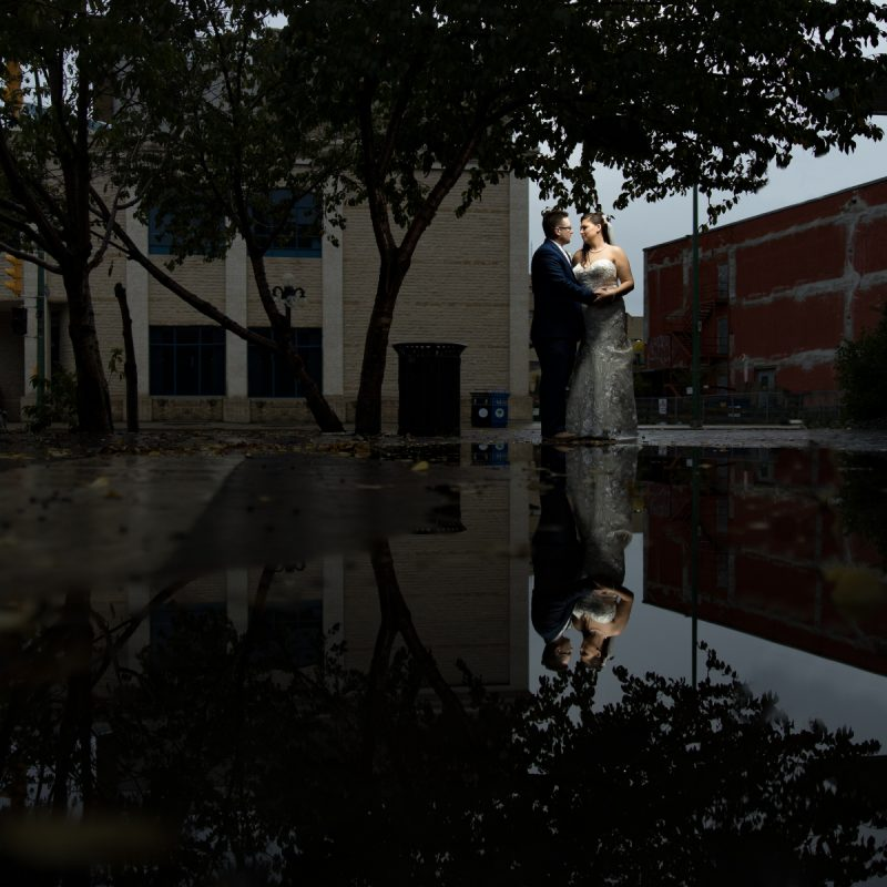 The couple embrace in front of a huge puddle with and their reflection