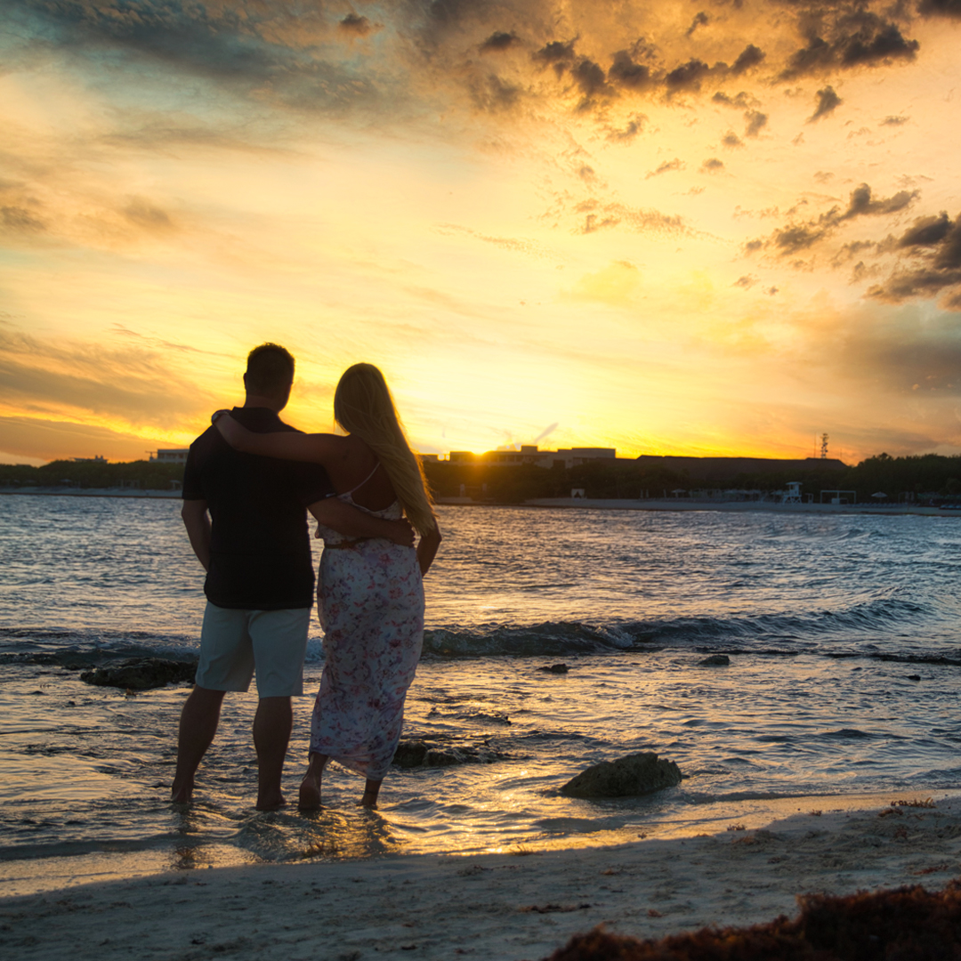Silvie and Lincoln dip their toes in the ocean as they watch the sunset in Mexico