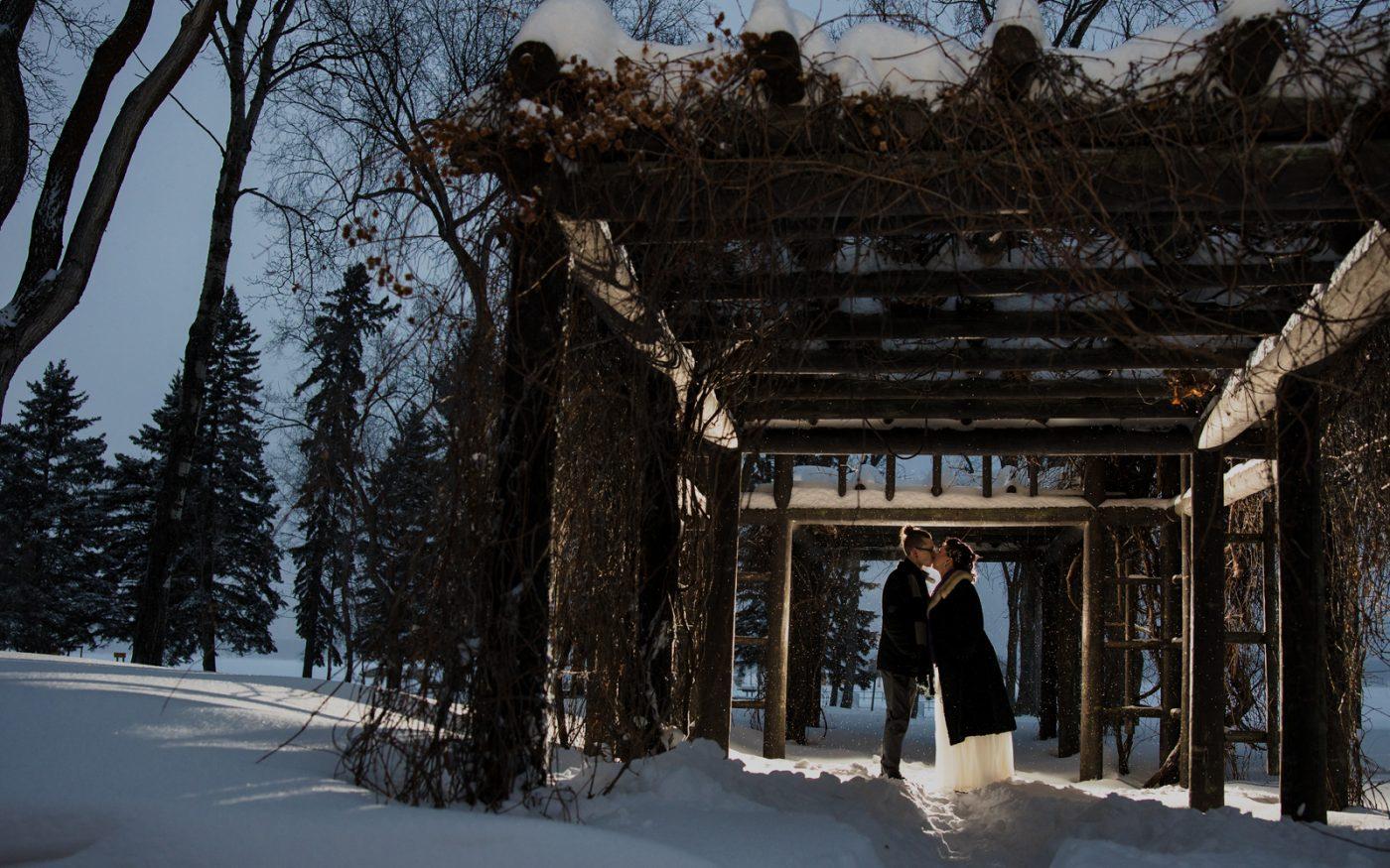 Robyn and Darryl kissing under a pergola
