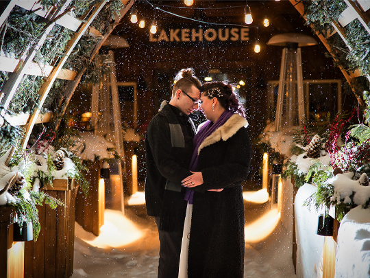 Robyn and Darryl cuddle close in front of the Lakehouse Lodge